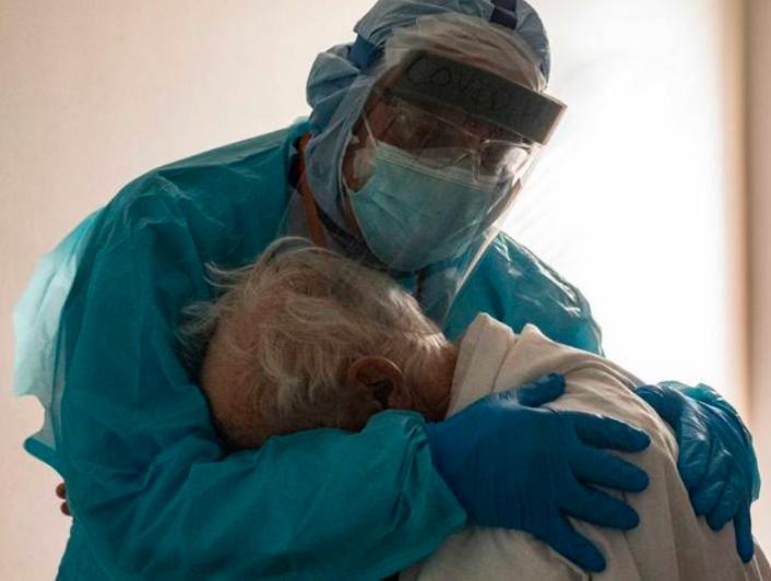 Se viraliza foto de médico abrazando a anciano con Covid-19